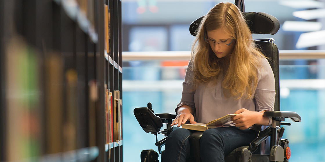 Teenage girl seated in a wheelchair, reading a book in a library.