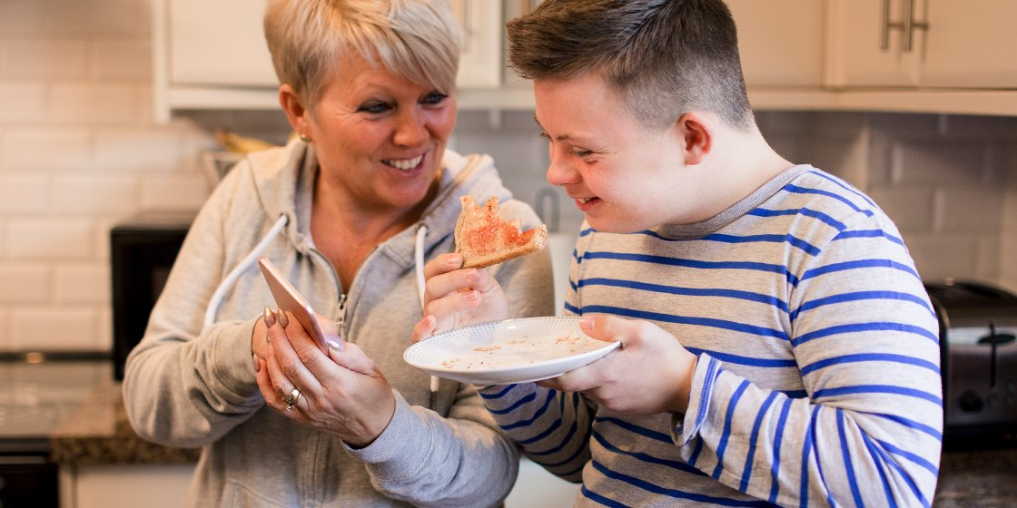 Mom and son with down syndrome standing in the kitchen smiling together