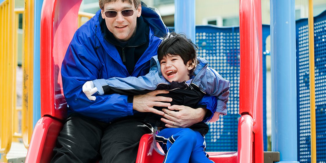 Father and young son on a playground slide. Son has cerebral palsy.