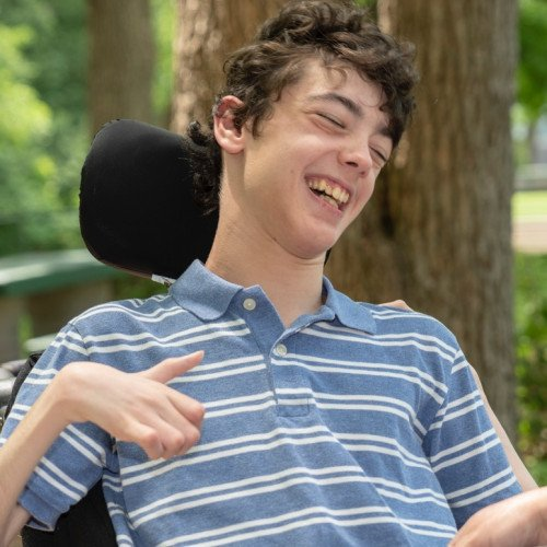 Teenager smiling in wheelchair.