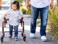 Young latino boy with down syndrome walks using a walker next to his father