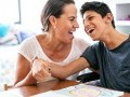 Mom and son smiling: son has a physical disability and is seated in a wheelchair.